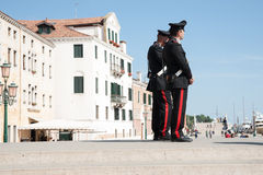 Two Carabinieri on steps near Venice waterfront. Stock Photos