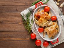 Two carcasses fried chicken in a bowl, baked chucks in an oven w. Ith tomatoes, with crispy crust, on dark brown wooden rustic table, top view, copy space for royalty free stock images