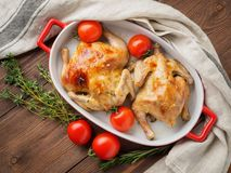 Two carcasses fried chicken in a bowl, baked chucks in an oven w. Ith tomatoes, with crispy crust, on dark brown wooden rustic table, top view royalty free stock images