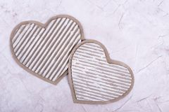 Two cardboard hearts. Handmade cardboard hearts on beige background. Loving hearts on the day of lovers stock image