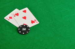 Two cards with a poker chip. On a green background Royalty Free Stock Photography