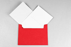Two cards  (Christmas and Silvester)  in red envel. Two greeting cards (Christmas and Silvester) in red envelope over gray background Stock Image