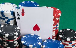 Two cards surrounded by poker chips on a green table stock photography