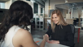 Two career women closing business deal with shaking hands inside office. Brunette woman in spectacles collects signed documents and pen on desk, congratulates stock video footage