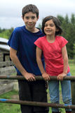 Two Carefree Country Kids. Two country kids, standing on a rungs of a gate. Shallow depth of field Stock Photography