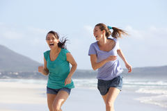 Two carefree friends running on the beach together. Portrait of two carefree friends running on the beach together Royalty Free Stock Photo