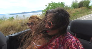 Two carefree girls partying while riding in cabriolet stock footage