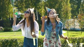 Two carefree young girlfriends having fun together blowing bubbles. With a toy bubble wand while enjoying a sunny day together outside, slow motion stock video footage