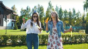 Two carefree young girlfriends having fun together blowing bubbles. With a toy bubble wand while enjoying a sunny day together outside stock footage