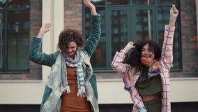Two carefree young women have fun and dance on the street. girlfriends have fun together. girls are walking in the. Two young women goofing around and having fun stock video