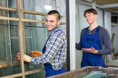 Two careful workmen cutting glass for windows Stock Photography