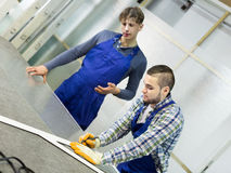 Two careful workmen cutting glass for windows Royalty Free Stock Images