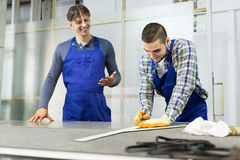 Two careful workmen cutting glass for windows Royalty Free Stock Photo