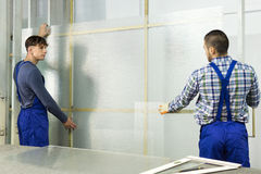 Two careful workmen cutting glass Royalty Free Stock Photos