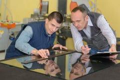 Two careful workmen work at pvc windows factory. Window royalty free stock image