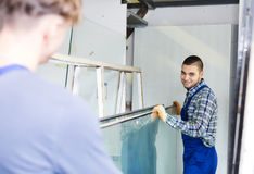 Two careful workmen working with glass Stock Photos