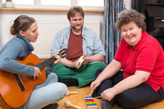 Two caretaker and a mentally disabled woman. Two caretaker and a mentally disabled women making a music therapy stock photo