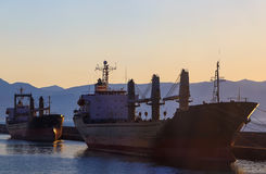 Two cargo ship in port of Heraklion City at sunset and the mountains. Greece. Royalty Free Stock Photos