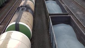 Two cargo trains on railway station. Oil cisterns standing and wagons with gravel moving. Transportation of construction materials. Industrial scene, top view stock footage
