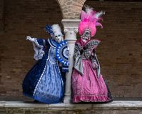 Two carnival-goers wearing brightly colored masks and costumes at Venice Carnival. Royalty Free Stock Photo