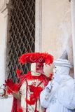 The two carnival masks discussing near the gate. royalty free stock image