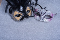 Two carnival masks with feathers   on glitter Royalty Free Stock Image