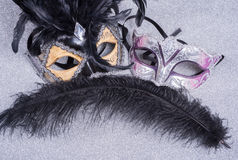 Two carnival masks with feathers   on glitter Royalty Free Stock Photo