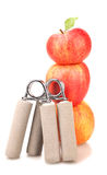 Two carpal expander and a stack of three red apples. With green leaf on white background fitness concept Stock Photo