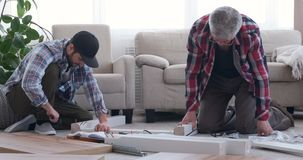 Two carpenter assembling furniture at home stock video footage