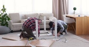 Two carpenter assembling table at home stock video