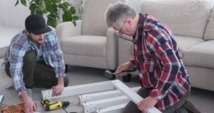 Two carpenters assembling furniture at home stock video footage