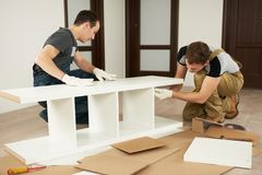 Two carpenters assembling furniture. In house Stock Images