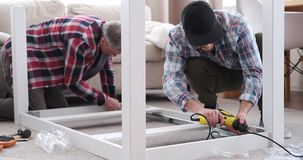 Carpenters assembling table at home. Two carpenters assembling table at home stock footage