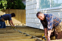 Two carpenters building a deck. Deck on house being built by two carpenters royalty free stock photography