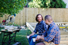 Two carpenters conversing over coffee. Two carpenters visiting with a cup of coffee stock photo
