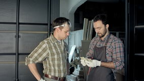 Two carpenters count money in workshop. stock footage