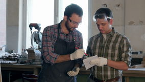 Two carpenters discuss something and write in notebook in workshop. stock footage