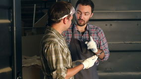 Two carpenters discussing something and watching something on the tablet in workshop. stock footage