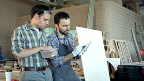 Two carpenters discussing work one of them eating and another writing in notebook. stock footage