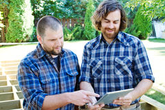 Two carpenters planning on tablet. Two carpenters working on a plan for deck stock images