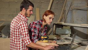 Two carpenters using laptop at their workshop while making furniture. Bearded male carpenter and his female colleague discussing work while making furniture royalty free stock images