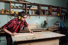 Two carpenters work hard in the workshop. A man and a woman. royalty free stock image