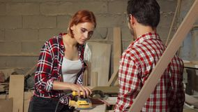 Two carpenters working on wood plank at the workshop. Beautiful young female carpenter polishing wood with random orbit sander, while talking to her male stock photos