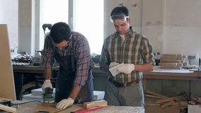 Two carpenters working with wooden planck and electric planer in workshop. stock video footage