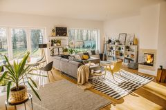 Two carpets on the floor in white Scandi living room interior wi. Th big window, glass door, corner sofa, fireplace and fresh plants royalty free stock photo