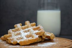 Two carrot waffles sprinkled with powdered sugar on a wooden board. Homemade waffles on a wooden plate. In the background is a gla stock images