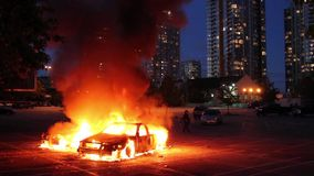 Two cars burn in parking lot with highrise at dusk stock video footage