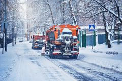 Two cars clean snow. Royalty Free Stock Images
