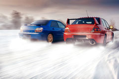 Two cars compete in race at winter sunset Stock Photo