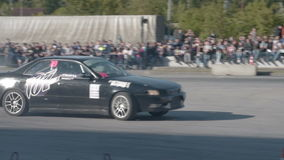 Two cars competing in drift. NOVOSIBIRSK, RUSSIA - JUNE 03, 2016: Two sport cars performing drifting skills during the championship stock video footage